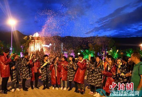 游客在丽江千古情景区身穿棉衣,围着篝火吃烧烤。丽江千古情景区供图