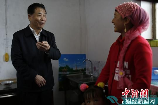 图为水利部部长鄂竟平在甘肃向一位农妇了解农村饮水情况。甘肃省水利厅供图